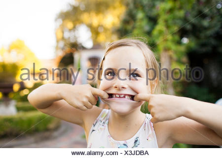 Portrait of girl pulling faces in garden - Stock Photo