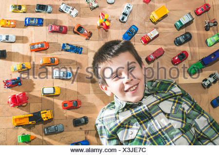 Boy lying on floor surrounded by toy cars - Stock Photo