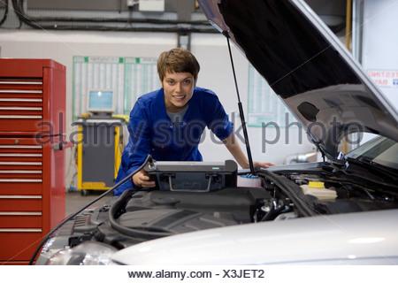Female mechanic with diagnostic computer by open bonnet of car, smiling, portrait - Stock Photo