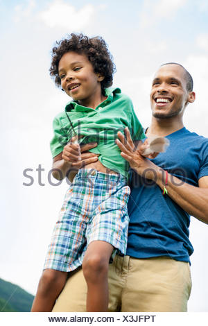 A man lifting his son up in his arms, playing outdoors. - Stock Photo