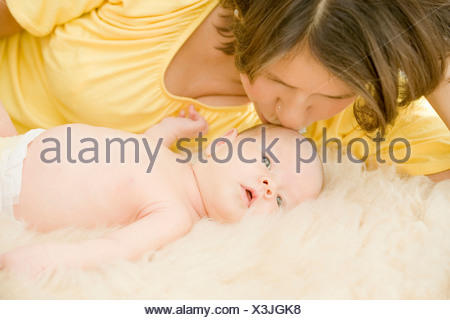 mother kissing her 1 month old baby on the brow - Stock Photo