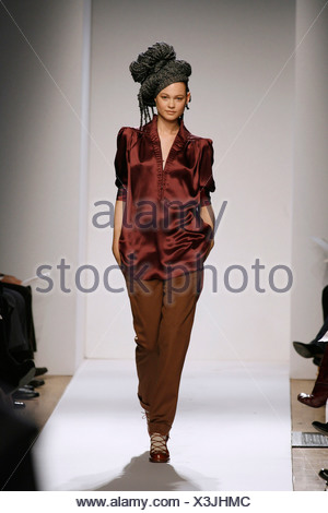 Anne Klein New York Ready to Wear Autumn Winter Model Behati Prinsloo wearing brown trousers, dark maroon red silk baggy top - Stock Photo