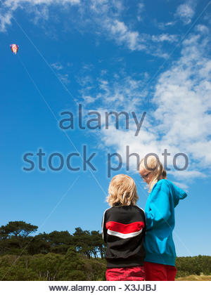 Sweden, Skane, Nyhamnslage, Two sisters (6-7, 10-11) flying kite - Stock Photo