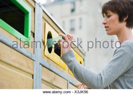 Woman placing plastic bottle in recycling bin - Stock Photo