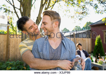 Homosexual couple hugging at backyard barbecue - Stock Photo