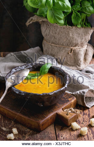 Ceramic bowl of carrot soup, served with fresh basil, croutons, kitchen towel and spoon on old wooden chair. Dark rustic style - Stock Photo