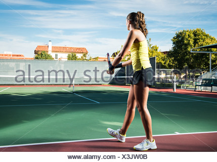 Female tennis player serving ball - Stock Photo