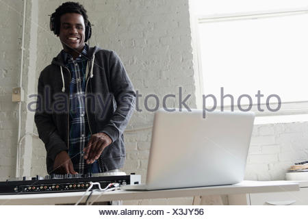 DJ using laptop and mixing desk - Stock Photo