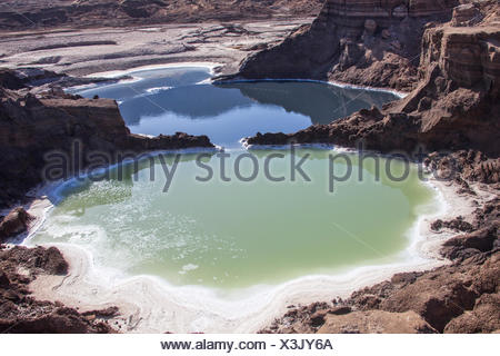 Water pools in sink holes on the shore of the Dead Sea, Israel - Stock Photo