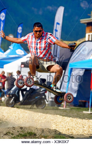 man jumping with an e-skateboard, France, Savoie - Stock Photo