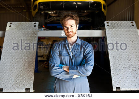Portrait of male mechanic behind car lift in garage - Stock Photo