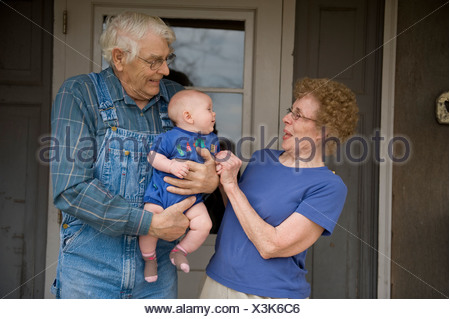 An elderly couple happily hold their granddaughter. - Stock Photo