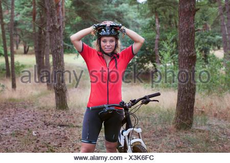 Portrait   woman mountain biker in forest - Stock Photo