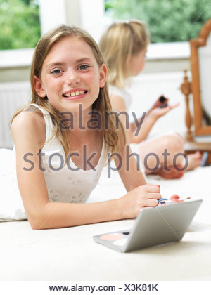 Girl smiling, putting on make-up - Stock Photo