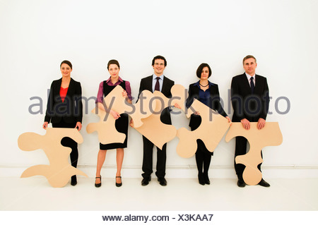Group of workers hold jigsaw pieces - Stock Photo