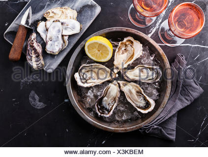 Opened Oysters on metal plate and rose wine on dark marble background - Stock Photo