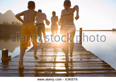 Family in swimwear running along jetty jumping into lake at sunset rear view lens flare - Stock Photo