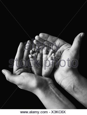 Baby's Feet In Mothers Hands - Stock Photo