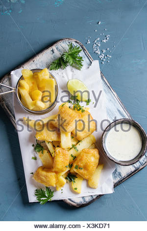 Traditional british fast food fish and chips. Served with white cheese sauce, lime, parsley, french fries in frying basket on white paper over blue co - Stock Photo