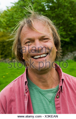 A man in casual clothes with blonde hair, smiling broadly. - Stock Photo