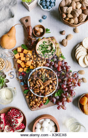 A bowl of spicy candied pecans are photographed as a part of a cheese and fruit board. - Stock Photo