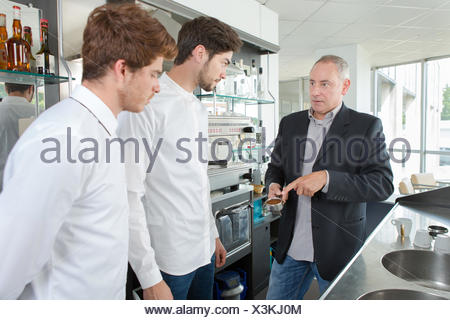 smiling waiters standing with teacher in cafe at school - Stock Photo