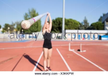 Female pole vaulter holding pole - Stock Photo