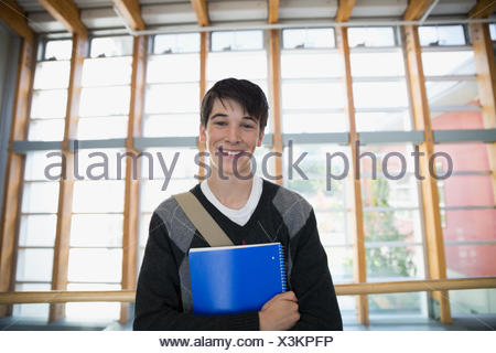 Portrait confident high school student with notebook - Stock Photo