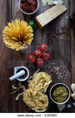 Pasta, pesto, garlic, tomatoes and parmesan on table - Stock Photo
