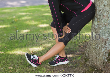 Low section of woman stretching her leg during exercise at park - Stock Photo