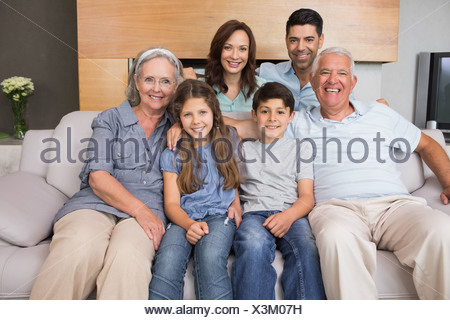 Portrait of smiling extended family on sofa in living room - Stock Photo