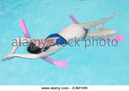 Pregnant woman exercising in swimming pool with flotation devices - Stock Photo