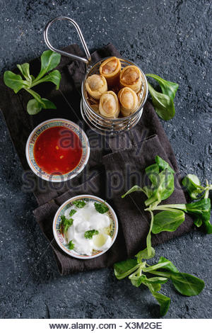 Fried spring rolls with red and white sauces, served in traditional china plate and fries basket with fresh green salad over black texture background. - Stock Photo