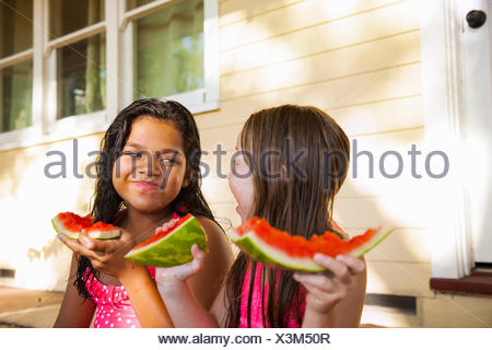 Two smiling girls sitting on house porch with slices of watermelon - Stock Photo