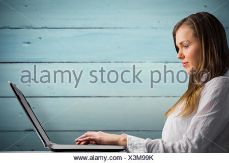 Composite image of businesswoman typing on her laptop - Stock Photo
