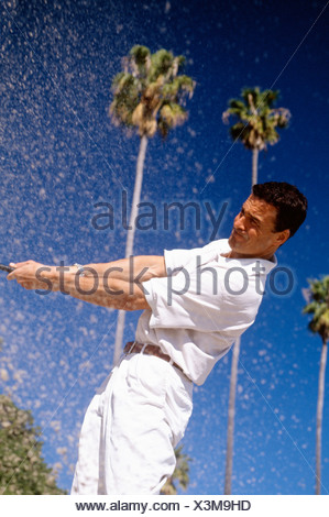 Man playing golf out of sand trap - Stock Photo