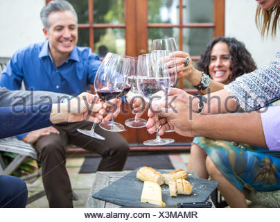 Mature adults friends making wine toast at garden party on patio - Stock Photo