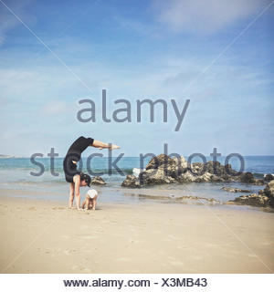 Mother and son doing yoga on beach, California, america, USA - Stock Photo