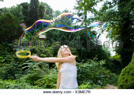 A girl making bubbles with a bubble wand - Stock Photo