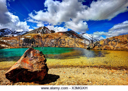 Volcanic stone lump in crystal clear Emerald Lake in the Tongariro national park, in the background of the Red Crater of the Mt. Ngauruhoe. - Stock Photo