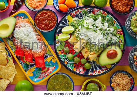 Green and red enchiladas with mexican sauces mix in colorful table. - Stock Photo