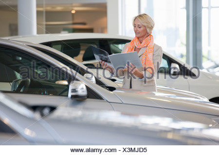 Customer looking at brochure next to car in car dealership showroom - Stock Photo