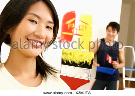 Portrait of a young woman smiling with a young man standing in the background - Stock Photo