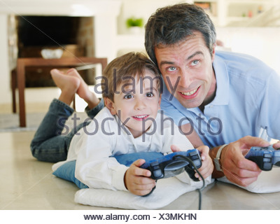 Father and son playing video game together - Stock Photo