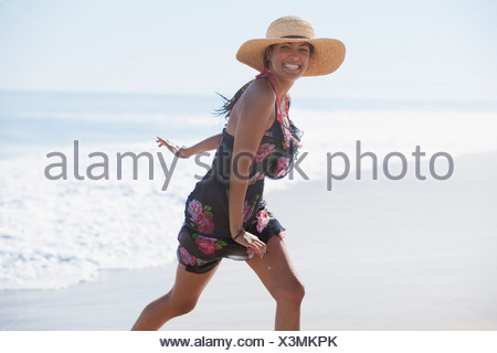 Woman running in waves on beach - Stock Photo