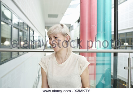 Young woman with blonde hair smiling, portrait - Stock Photo