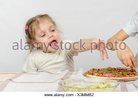 Little girl with tongue sticking out a hand to pull the pizza, which prepares her older sister - Stock Photo
