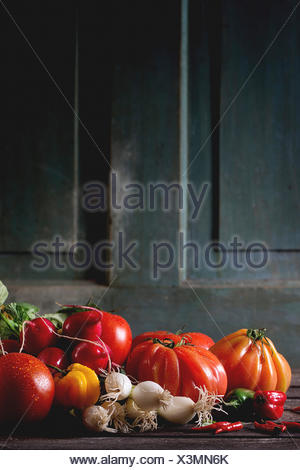 Heap of fresh ripe colorful vegetables tomatoes, chili peppers, green onion and bunch of radish over old wooden table. Dark rust - Stock Photo
