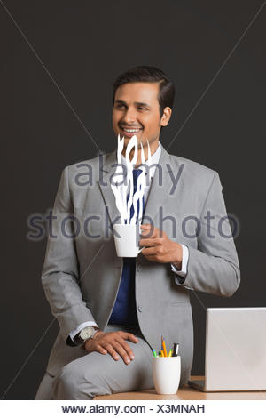 Digitally generated image of businessman having coffee in office - Stock Photo