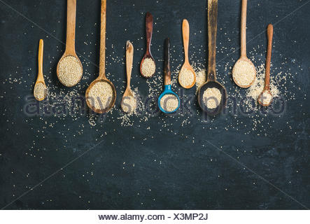 Quinoa seeds in different spoons over black stone background, top view, copy space. Superfood, healthy eating, dieting, clean eating, detox or vegetar - Stock Photo